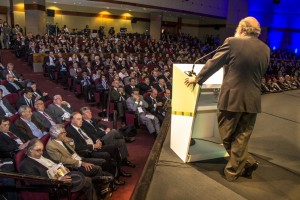 Behind older man speaking - large audience
